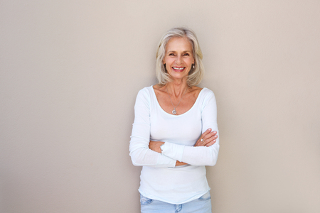 Foto per Portrait of beautiful older woman standing and smiling with arms crossed - Immagine Royalty Free