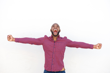 Photo pour Portrait of excited young african man with arms outstretched shouting against by white wall - image libre de droit