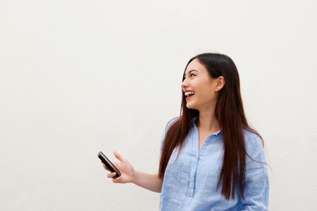 Photo for Close up side portrait of laughing woman with long hair holding mobile phone - Royalty Free Image