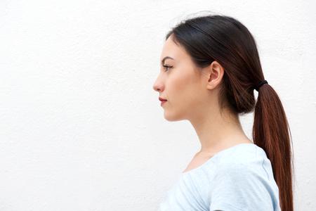 Foto de Close up side portrait of casual young woman standing alone - Imagen libre de derechos