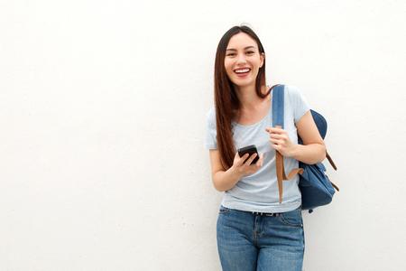 Foto de Portrait of happy young woman standing with backpack and mobile phone - Imagen libre de derechos