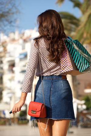Photo pour Rear portrait of woman walking in jean skirt with gift bags and cellphone - image libre de droit