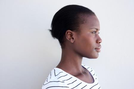 Photo pour Close up profile image of young black woman against white wall - image libre de droit