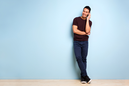 Foto de Full body portrait of stylish mature asian man standing by blue wall and making a phone call - Imagen libre de derechos
