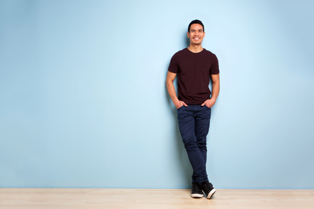 Photo pour Full body portrait of fashionable asian man standing with hands in pocket by the blue wall - image libre de droit