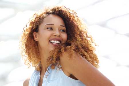 Photo pour Close up portrait of happy young woman with curtly hair looking over shoulder - image libre de droit