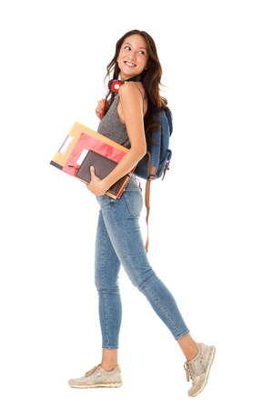 Foto de Full length portrait of smiling asian college student walking against isolated white background with books and bag - Imagen libre de derechos