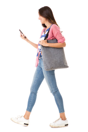 Photo pour Full body side portrait of fashionable young asian woman walking with purse and mobile phone against isolated white background - image libre de droit