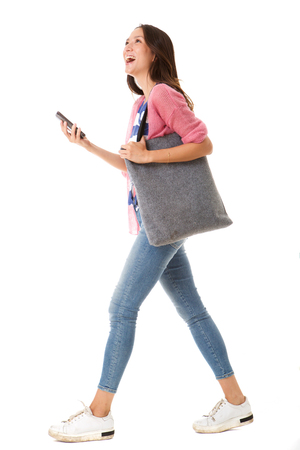Photo for Full body side portrait of fashionable young asian woman walking with purse and smart phone against isolated white background - Royalty Free Image