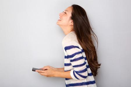 Foto de Side portrait of pretty asian woman smiling with smart phone against gray background - Imagen libre de derechos