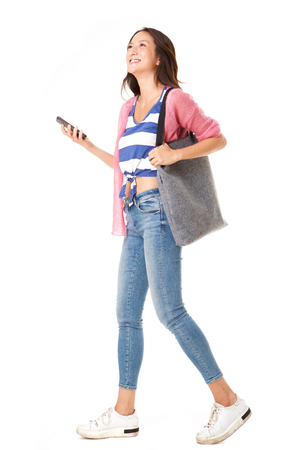 Photo for Full body side portrait of fashionable young asian woman walking with handbag and mobile phone against isolated white background - Royalty Free Image