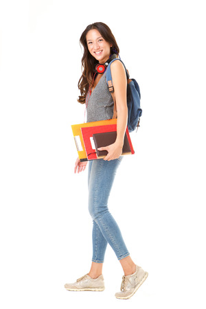 Photo pour Full body side portrait of asian female college student walking against isolated white background with books and bag - image libre de droit