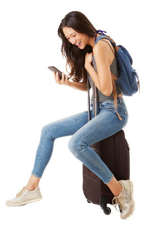 Foto de Full body side portrait of happy asian female traveler sitting on suitcase and looking at cellphone against isolated white background - Imagen libre de derechos