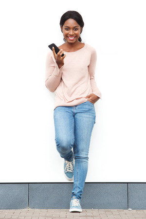 Photo pour Full length portrait of smiling young black woman standing against white wall with cellphone - image libre de droit