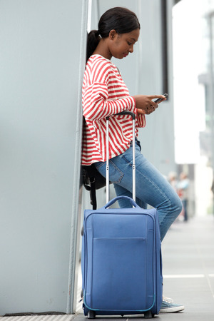 Photo for Full length side portrait of young woman traveling with suitcase in airport looking at cellphone - Royalty Free Image
