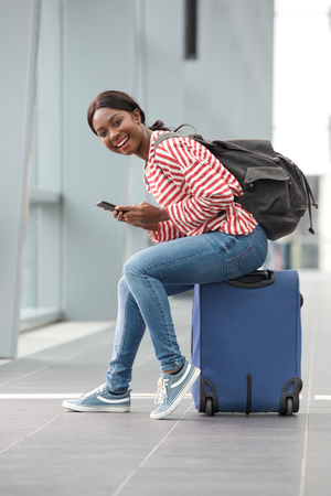 Photo pour Portrait of happy young black woman sitting on suitcase with mobile phone at station - image libre de droit