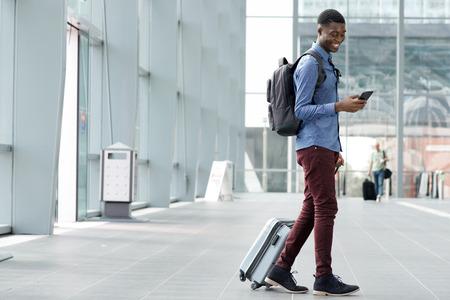Foto de Full body side portrait of young black man traveling with suitcase and cellphone at airport - Imagen libre de derechos