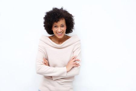 Photo pour Portrait of older woman smiling with arms crossed against white background - image libre de droit