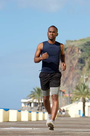 Foto de Full body portrait of healthy young african american man running outside - Imagen libre de derechos