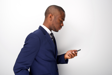 Foto de Side portrait of young black businessman looking at mobile phone - Imagen libre de derechos