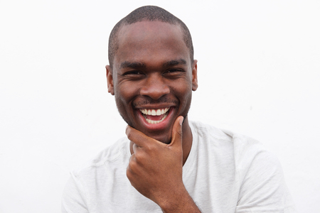 Photo pour Close up portrait of handsome young black man smiling with hand to chin - image libre de droit