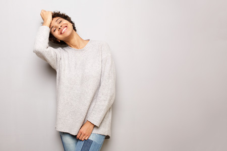 Photo pour Portrait of beautiful young woman smiling by gray wall with sweater - image libre de droit