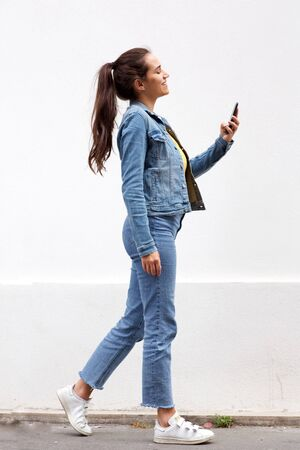 Foto de Full length portrait of young woman with brown hair walking and looking at mobile phone by white wall - Imagen libre de derechos