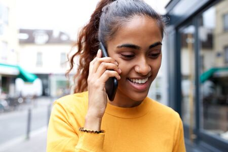 Photo pour Close up portrait of happy young woman talking with smart phone in city - image libre de droit