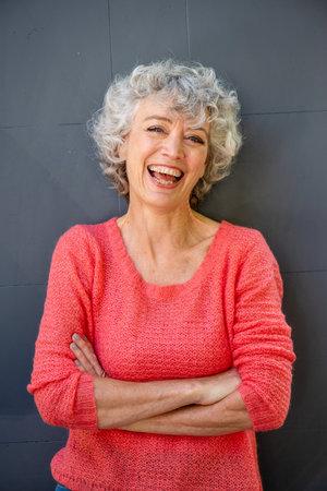 Foto de Front portrait of attractive middle aged woman laughing with arms crossed - Imagen libre de derechos