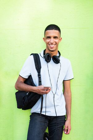 Photo pour Portrait of smiling North African male college student against green background with mobile phone and bag - image libre de droit