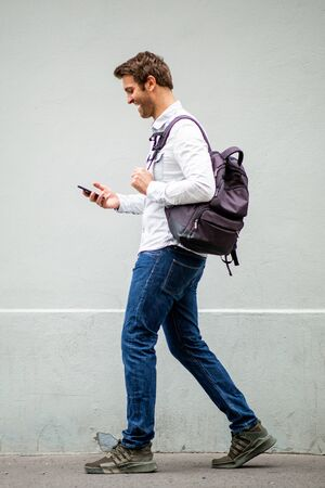 Photo pour Full body portrait of happy travel man with bag looking at mobile phone by gray wall - image libre de droit