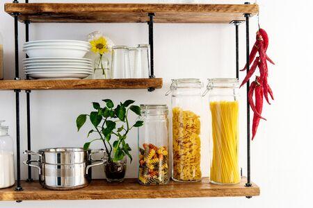 Photo pour Pots and glass jars with cereals and pasta on shelves - image libre de droit