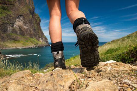 Photo pour Behind of female hiker shoes walking towards water - image libre de droit