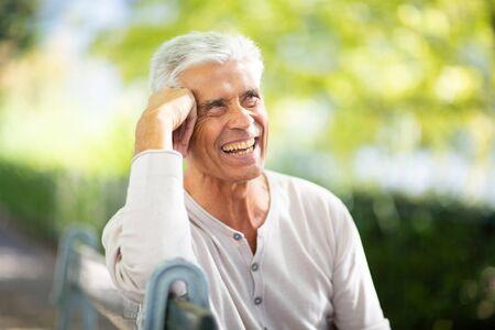 Photo pour Close up portrait handsome older man sitting on park bench and smiling - image libre de droit