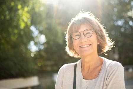 Photo pour Close up portrait smiling older woman outside with glasses - image libre de droit