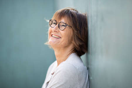Photo for Close up side portrait smiling older woman with eyeglasses leaning against wall - Royalty Free Image