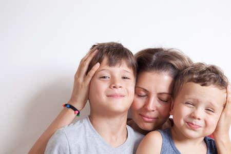 Foto für Portrait of happy mother with cute kids boy sitting on a light background. Happy family concept. - Lizenzfreies Bild