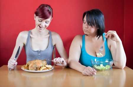 Tailored diet. Skinny woman is happy because she can eat huge meals, while the overweight woman is looking sadly at her because she has to eat just a few leaves of lattuce.