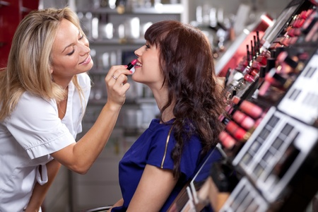 Make up artist applying lipstick to a customer in a beauty store  Selective focus