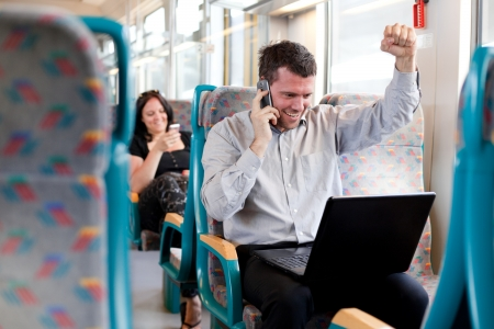 Happy businessman receiving good news on a train. selective focus.
