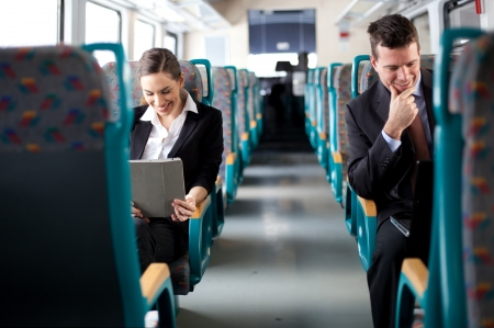 Business on the move  Business people using computers on the train  Selective focus