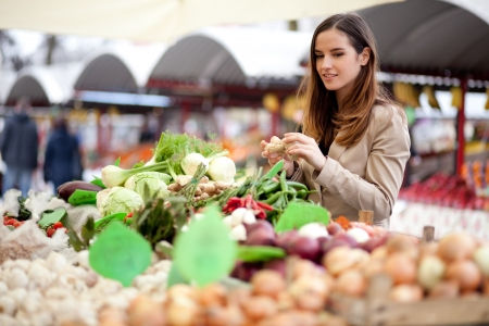 Young woman picking fresh produce at the market