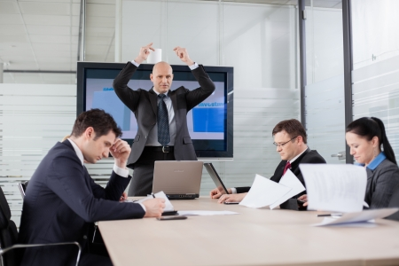 Angry and disappointed boss throwing documents during briefing