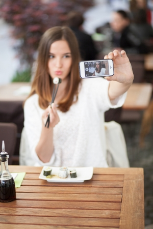 Young woman taking a self portrait in a sushi restaurant