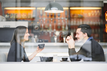 Couple in love drinking coffee laughing in cafe