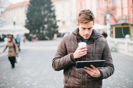 Young man using tablet computer on street