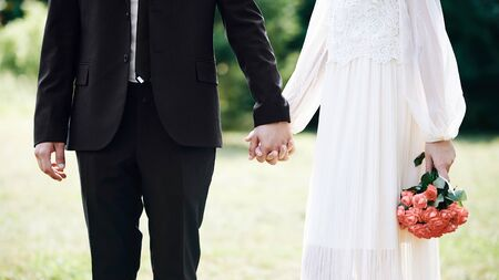 Photo pour Lovers holding hands in summer park. Weddind day with beautiful classic style. Beautiful bride in white dress with roses bouquet. - image libre de droit