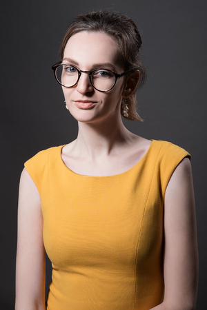 Portrait of attractive young woman girl in yellow dress isolated on dark grey background in glasses. teacher profession