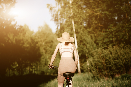 Funny girl driving bicycle outdoor. Sunny summer lifestyle concept. Woman in dress and hat in Field with dandelions. Female ride in park. Light photo effect for text. Copyspace for design