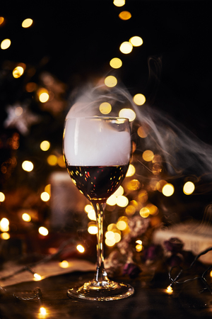 Festive atmosphere in the evening with a glass of red wine. Smoke creeping into clubs in glass and light bokeh background. Christmas, New Years or Saint Valentine holiday.Golden color and soft focus.